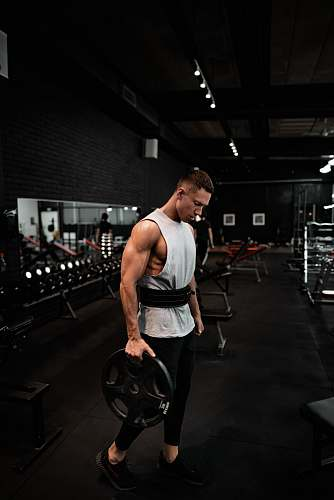 photo human man in white tank top holding bumper plate fitness free for commercial use images