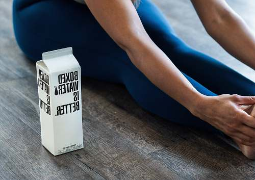 photo human person wearing blue leggings sitting near boxed water apparel free for commercial use images