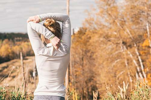 human woman standing while stretching beside brown leafed trees people