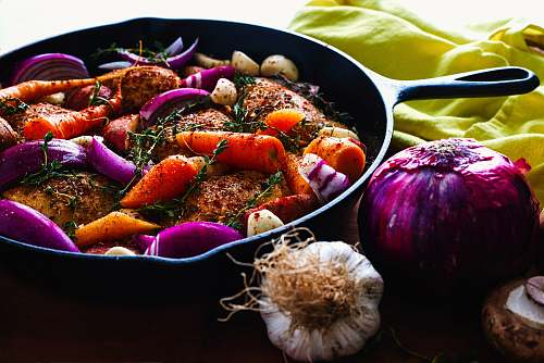 food carrots, garlic, onions, and herb spicing meat on skillet vegetable