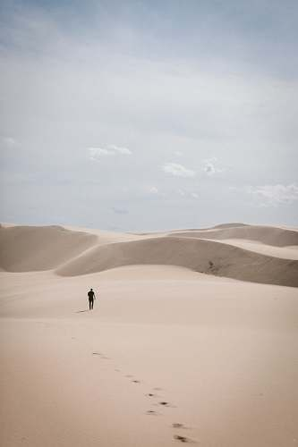 grey person waling on desert dune