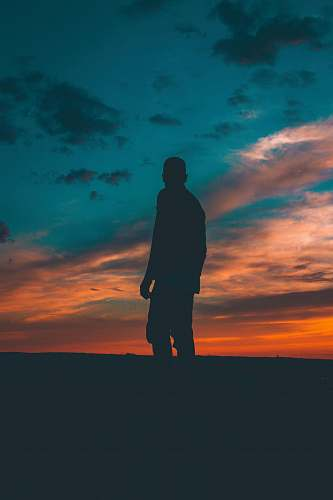 photo cloud silhouette on man standing on ground dark free for commercial use images
