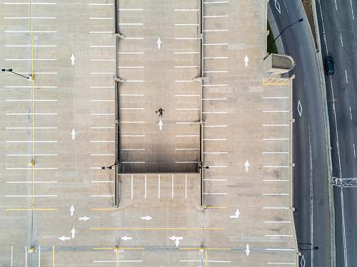 car person lying on gray concrete parking area in aerial photography drone