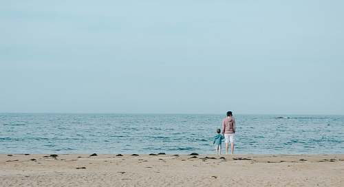 coast man and toddler standing on shore ocean