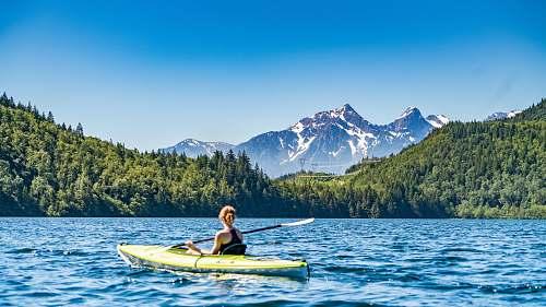 lake woman kayaking on lake during daytime mountain
