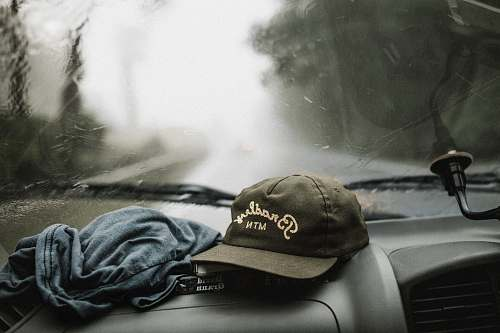 cap black and white baseball cap near grey shirt on top of glove compartment inside car trip