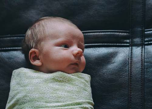 baby baby covered in green blanket on black leather surface newborn