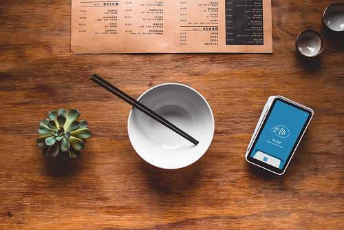 electronics black chopsticks in white ceramic bowl on table phone