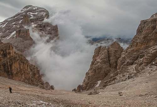 slope landscape photography of foggy mountain rocks cloud