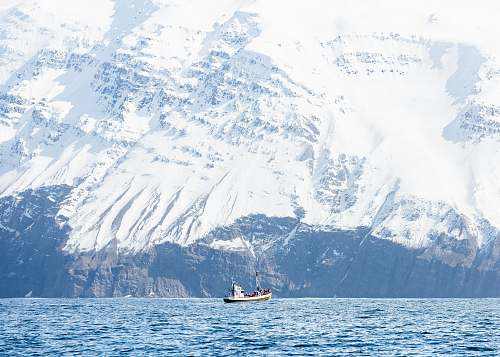 snow white boat on body of water bear mountain covered of snow mountain