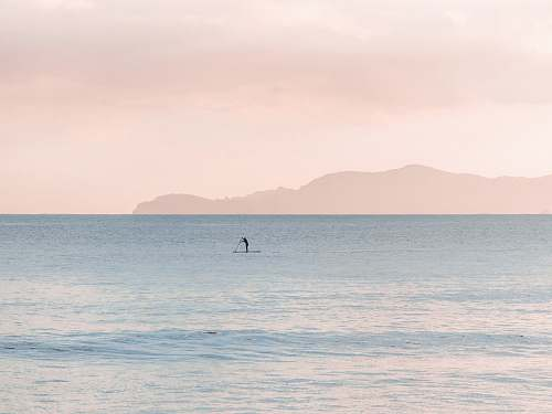 sea person paddle boarding during daytime pastel