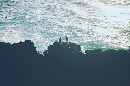 sea two person standing on the cliff near the ocean rocks
