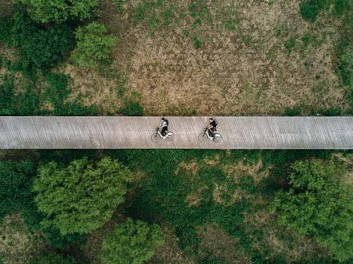 boardwalk aerial view photography of two person on road bicycle
