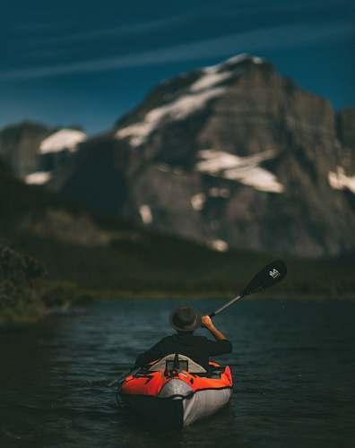 canoe man riding on inflatable kayak beside mountain kayak
