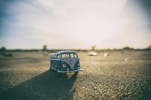 miniature shallow focus photography of white and teal die-cast Volkswagen Samba with sunlight vw bus