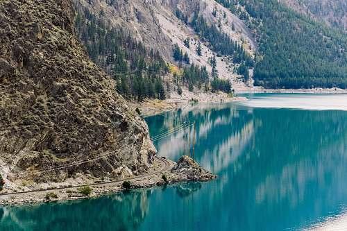 reflection river beside rock mountain lake