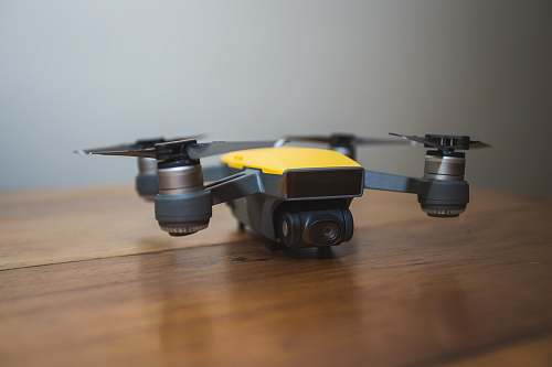 hardwood yellow and black DJI drone on wooden surface quadcopter