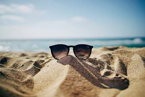 photo sunglasses black Ray-Ban Wayfarer sunglasses on beach sand beach wallpapers free for commercial use images