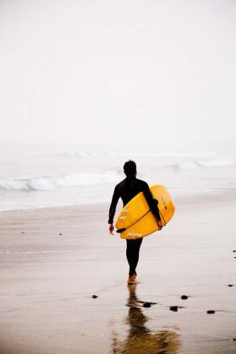 photo sea man holding yellow surfboard while walking on seashore during daytime surfing free for commercial use images