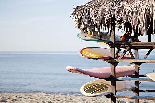 sea red and white surfboard in brown wooden rack summer