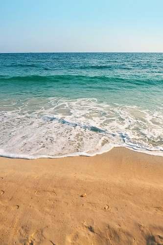ocean seashore under clear blue sky during daytime water