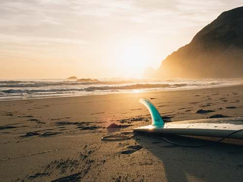 photo ocean surfboard on brown sand beside ocean during sunset nature free for commercial use images
