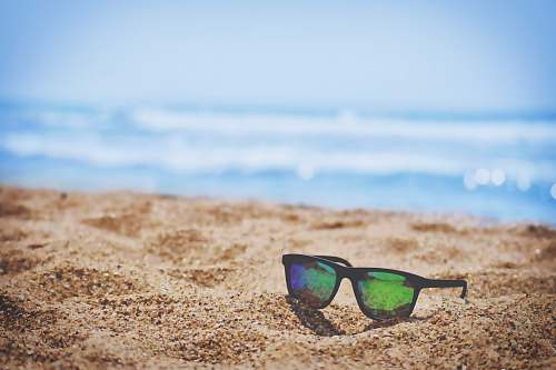 photo summer wayfarer sunglasses on beach sand during daytime sunglasses free for commercial use images