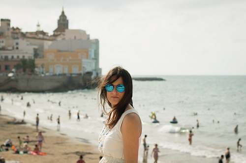 coast woman in white sleeveless top near seashore people