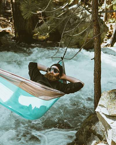 photo transportation man reclining on blue and brown hammock vessel free for commercial use images