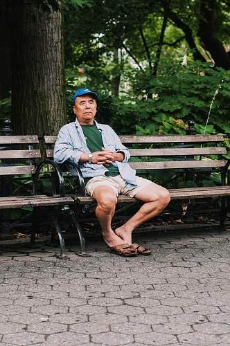 human man sitting on bench closing his eyes near trees people