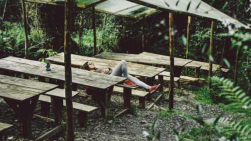 plant woman lying on gray wooden picnic table sleep
