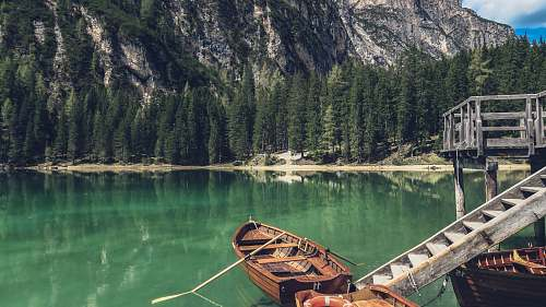 italy brown canoe docking on gray wooden staircaes rowboat