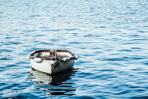 photo water white wooden boat on body of water ocean free for commercial use images