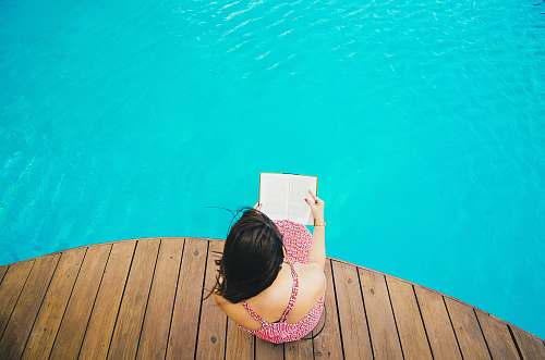 photo blue woman sitting on poolside dock while riding book woman free for commercial use images