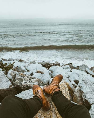 boots person sitting front of seashore waves