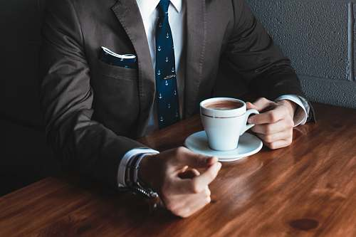 business man holding cup filled with coffee on table hand