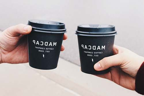 photo cup two person holding black Madcap coffee disposable cups hand free for commercial use images