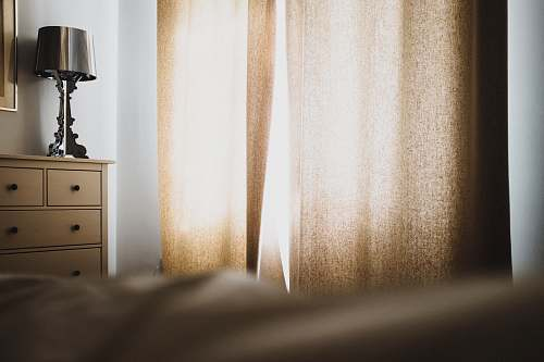 bed brown window curtain near dresser and table lamp home decor