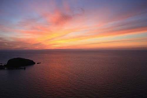 sunrise body of water during horizon dawn