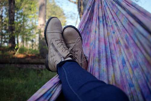 nature person lying on pink and purple hammock surrounded with trees boots