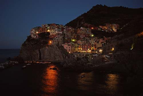 photo village concrete houses on rocky hill beside large body of water during nighttime town free for commercial use images