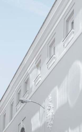 spain white street lamp mounted on white building wall corner