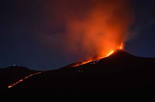 eruption black mountain with flowing lava at nighttime italy