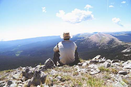 mountain person sitting on a gray rock watching over a mountain mountains