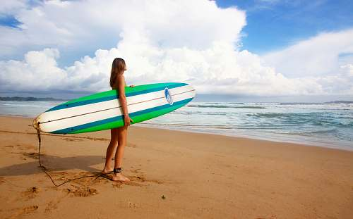 photo beach woman standing near sea holding white, blue, and green surfboard under blue sky coast free for commercial use images