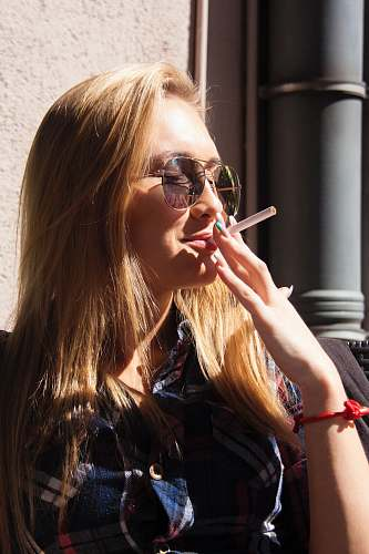 photo person close-up photography of woman holding cigarette stick during daytime human free for commercial use images