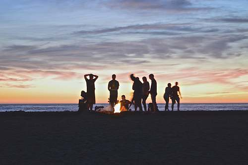 photo sunset group of people setting up campfire beach free for commercial use images