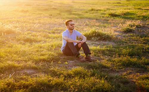 photo person man sitting on green grass field human free for commercial use images