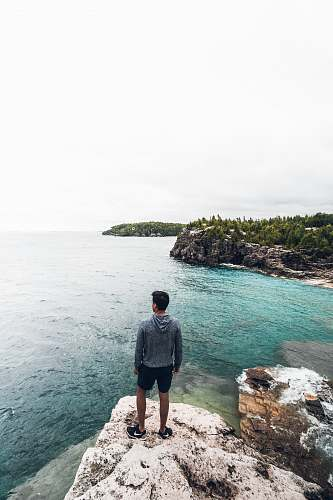 photo person man standing on white and brown rock seeing horizon during daytime water free for commercial use images