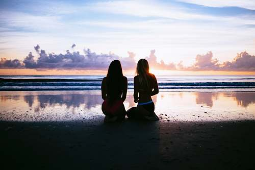 photo human silhouette of two women facing body of water beach free for commercial use images